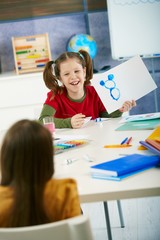 Happy elementary age schoolgirl in art class