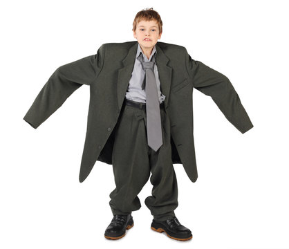 little boy in big grey man's suit and boots nads at sides