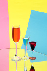 Three wine-glasses on multi-coloured background