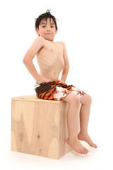 Boy in Swim Suit Sitting on Box