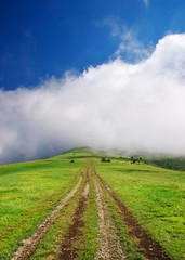 Road on hill leaves in cloud on horizon.