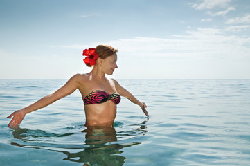 Sexy red girl wearing bikini standing in the ocean
