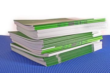 Pile of green magazines isolated on white background