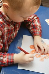 Little Boy In Drawing A Halloween Picture In His Class