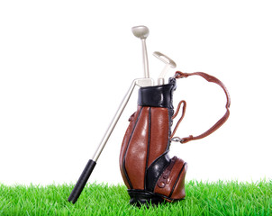 Golf equipment in a leather bag on a green lawn isolated over wh