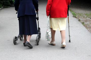 Zwei alte Frauen mit Gehwagen und Stock im Park