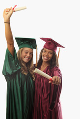 two female graduates in cap and gown with diplomas