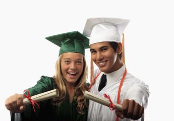 two graduates in cap and gown with diplomas