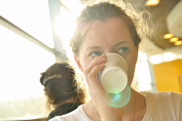 woman is drinking from paper cup