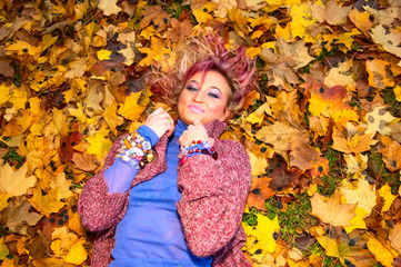 young smiling woman on maple leaves