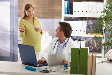 Pregnant woman consulting with doctor.