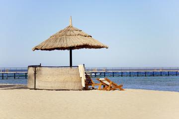 chaise-longe and umbrella on beach.