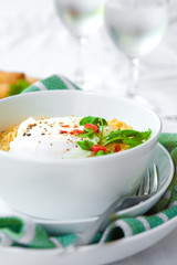 A bowl of spicy oriental noodles with poached egg