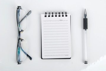 glasses,pen with notebook