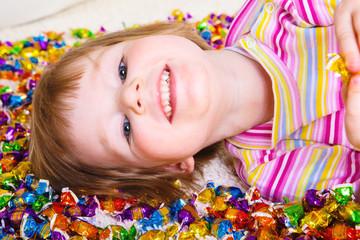 Kid lying among candies