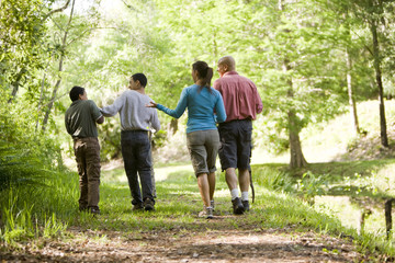Hispanic Family Walking Along Trail In Park