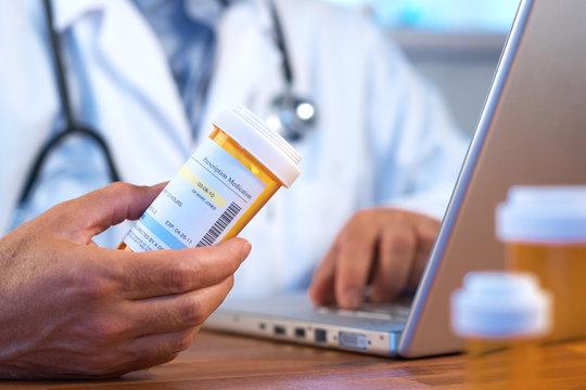 Doctor holding prescription bottle with laptop