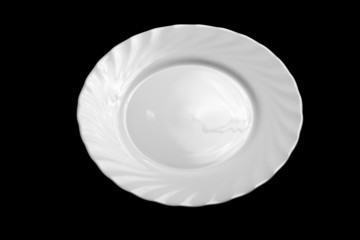 Round white plate isolated on black background