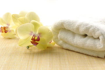 towel and orchids on bamboo mat