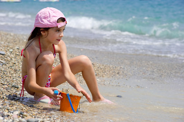 little girl play with sand - bambina in spiaggia