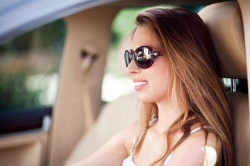 Beautiful woman driving car with sunglasses on