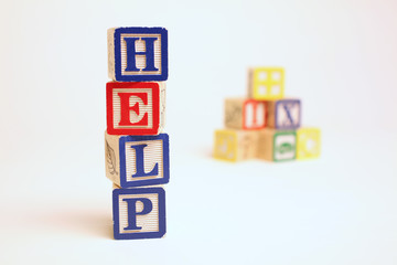 HELP spelled with child's cubes
