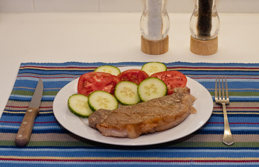 Strip Steaks Tomatoes and Cucumbers