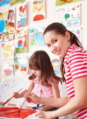 Child painting with teacher in preschool.