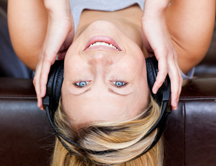 Delighted woman lying on a sofa and listen to music