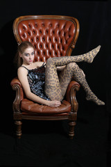 Beautiful model, photographed sitting on a big Chair