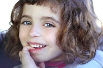 little firl smiling shy biting finger blue eyes