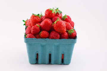 Fresh isolated red strawberries in a pint