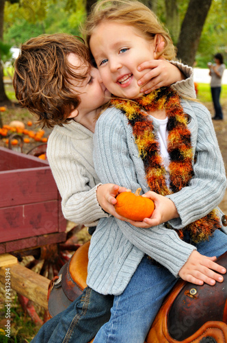 Little boy giving little girl a pumpkin and a kiss on a wagon little boy giving little girl a pumpkin and a kiss on a wagon altavistaventures Images