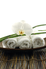 Bowl of towel and orchid on mat
