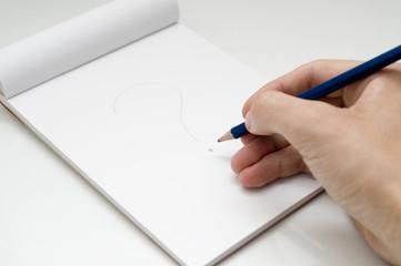 dibujando interrogante con un lapiz en un bloc de notas