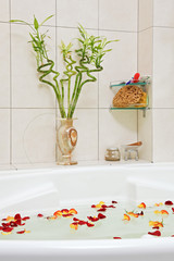 Part of bathroom with rose petals floating in water
