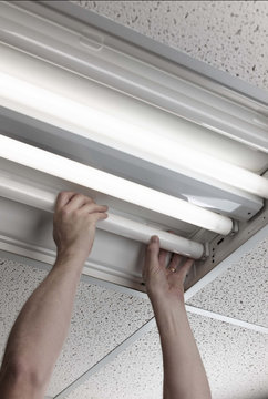 man installs fluorescent lamp in ceiling ballast