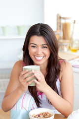 Cute woman holding a cup a coffee in the kitchen