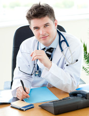 Serious male doctor writing a precreption