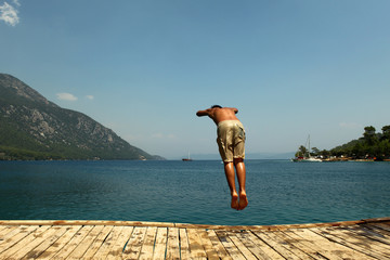 Young man jump diving from pier into sea