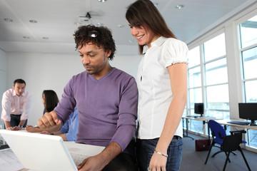 Homme et femme d'affaires devant un ordinateur portable