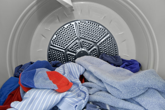 Clothes including shorts, shirts and towels in laundry dryer.   Fresh, clean and ready to fold.