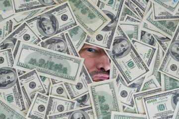 man looking through a hole between dollar bills
