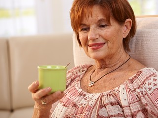 Portrait of elderly woman drinking coffee