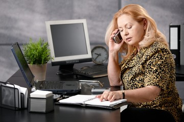 Senior woman calling in office