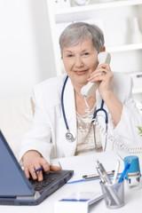 Senior doctor talking on phone