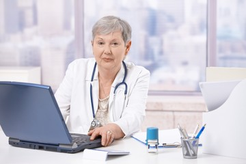 Senior doctor using laptop computer