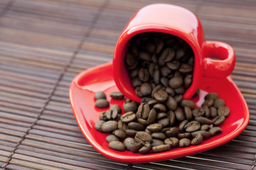 cup and saucer and coffee beans on a bamboo mat