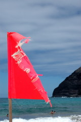 A tattered red warning flag at a beach