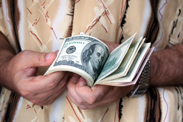 Sheaf of dollars in hands of the man